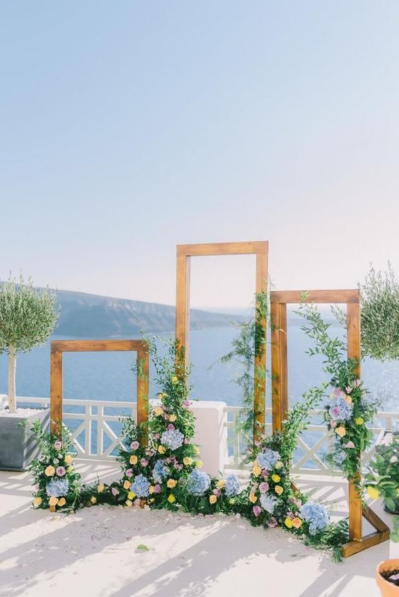 a chic wedding altar of wooden frames, blue and yellow blooms and lush greenery with a gorgeous sea view