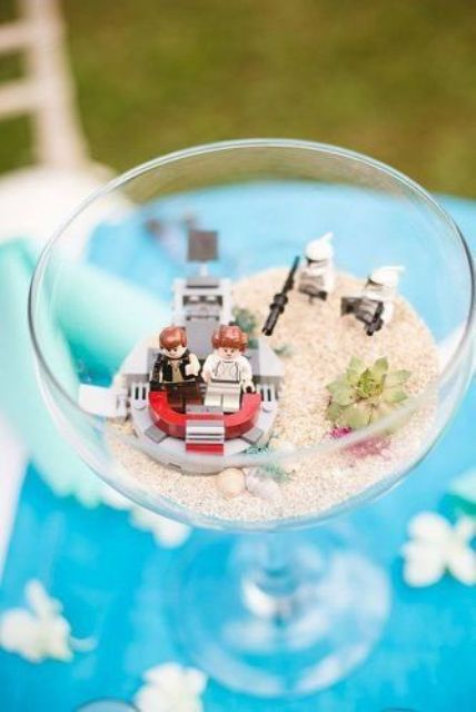a cool wedding decoration of a large glass with sand, a succulent and some fun Star Wars figurines