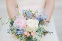 a cute pastel bouquet with blue and pink blooms, a white rose, some thistles and greenery
