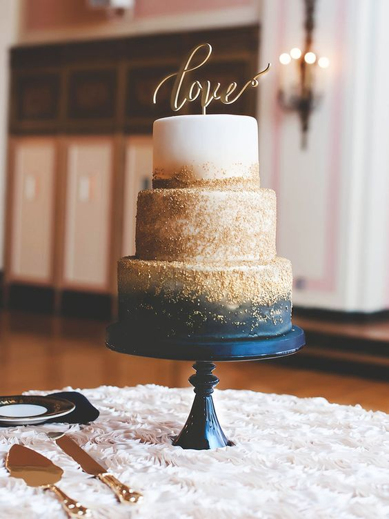 a dreamy navy, white and gold glitter wedding cake with a gold calligraphy cake topper is a gorgeous idea for a glam wedding in these colors