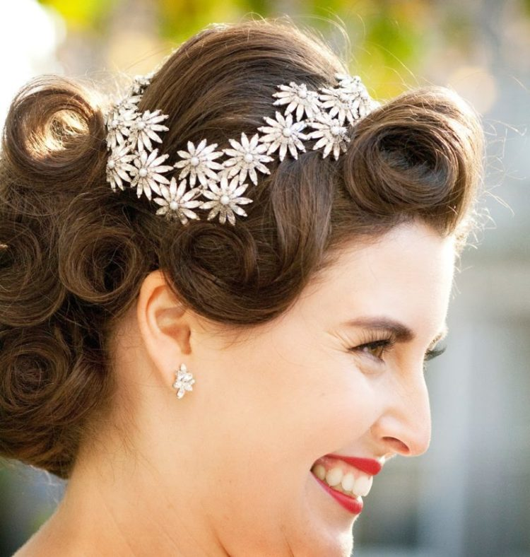 a fully curled wedding updo with a volume on top and a shiny flower hairpiece