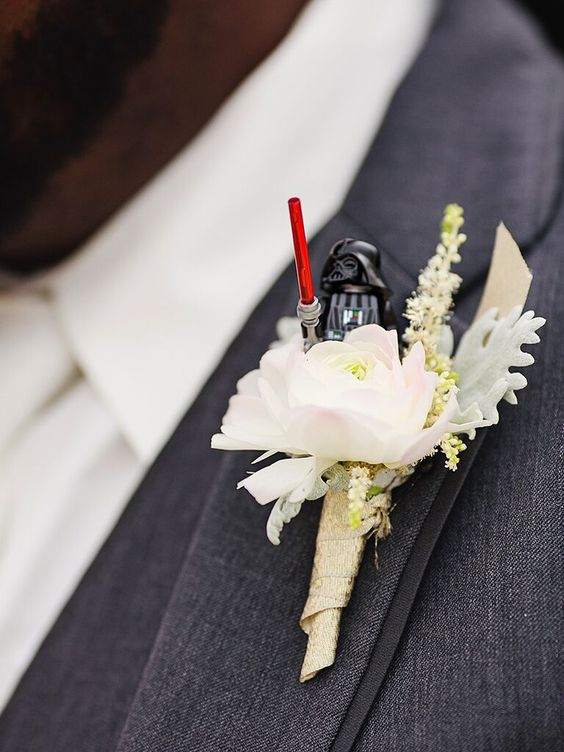 a funny wedding boutonniere of a blush bloom and a Star Wars Lego figurine