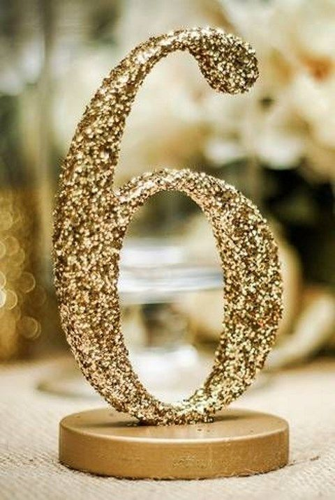a gold glitter table number on a stand is a shiny and glam idea for reception tables and it can be easily DIYed