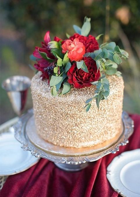 a gold glitter wedding cake with red blooms, greenery and berries on top is a glam, chic and cool idea to rock