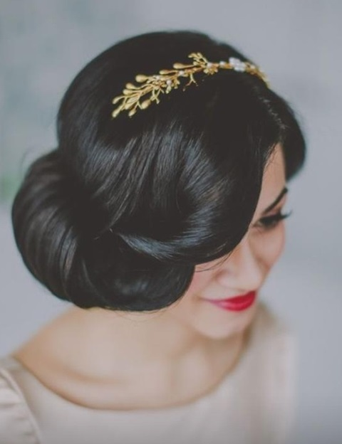 a gorgeous curled updo with a twisted front and a gold headpiece with rhinestones