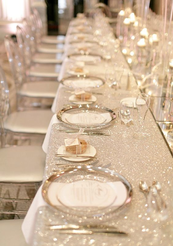 a gorgeous glam wedding tablescape with a white glitter tablecloth, silver rimmed plates, silver cutlery, floating candles and chic glasses