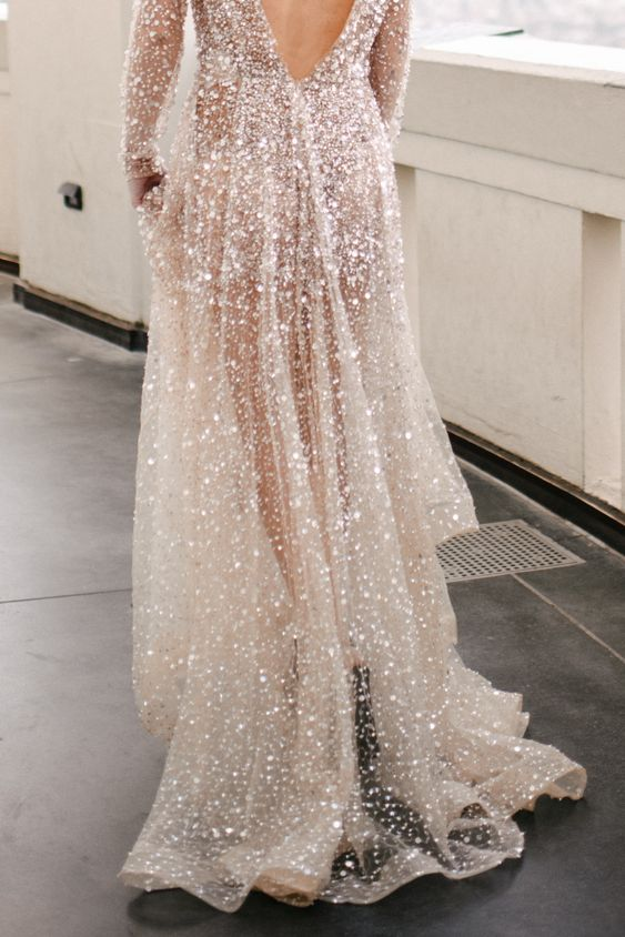 a gorgeous glitter A-line wedding dress with a cutout back, long sleeves and a train is a very pretty glam idea to rock