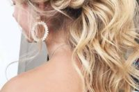a gorgeous low wavy ponytail with a messy bump and a twisted braid on the side is a trendy idea