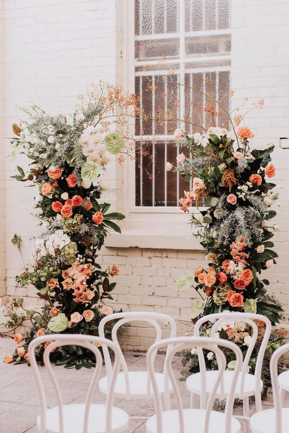 a gorgeous lush wedding altar decorated with greenery, white, coral and blush blooms and blooming branches