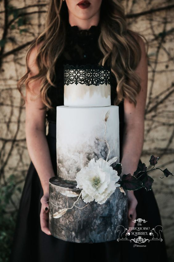 a gorgeous moody wedding cake with watercolor dark florals, sugar blooms and leaves and a black lace top