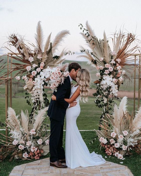 a gorgeous wedding altar of lush blush and pink blooms, pampas grass and gilded fronds for a touch of boho