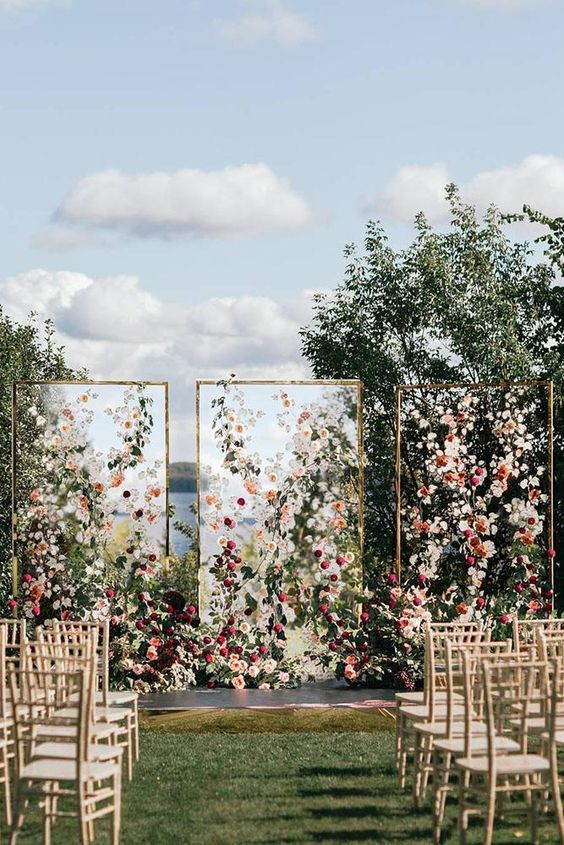 a gorgeous wedding backdrop of three sheer screens with lots of blush and burgundy blooms and greenery