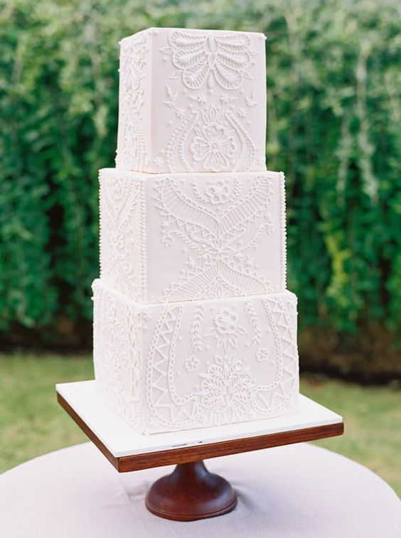 a gorgeous white square wedding cake all covered with lace looks like a real statement