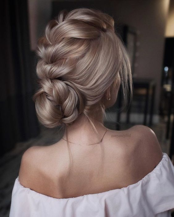 a low bun with a large dimensional braid on top forming a bun and ome locks down looks very chic