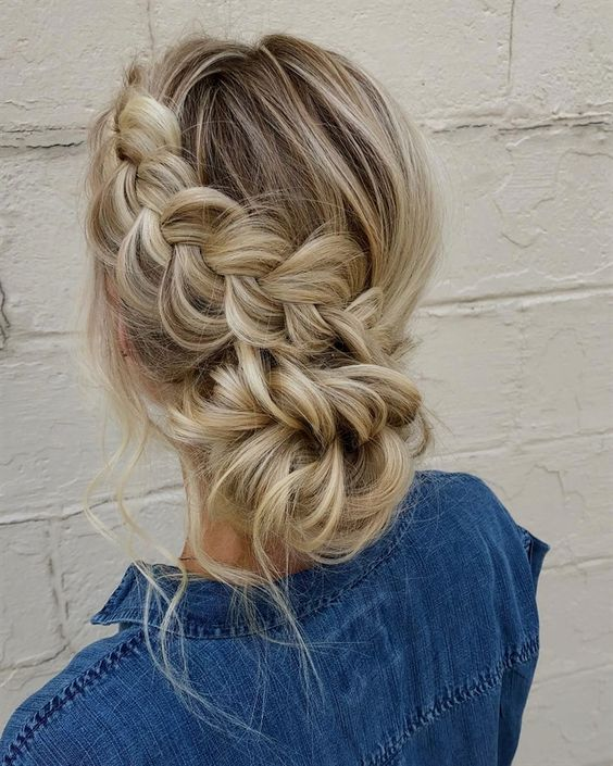 a low bun with a side dimensional braid that forms a bun is a cute boho idea