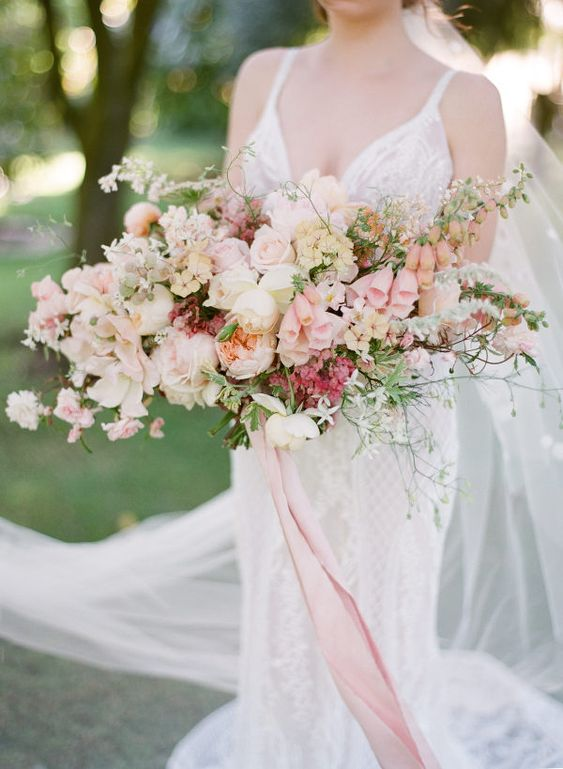 a lush and oversized blush wedding bouquet with neutral blooms and lots of greenery plus long ribbons