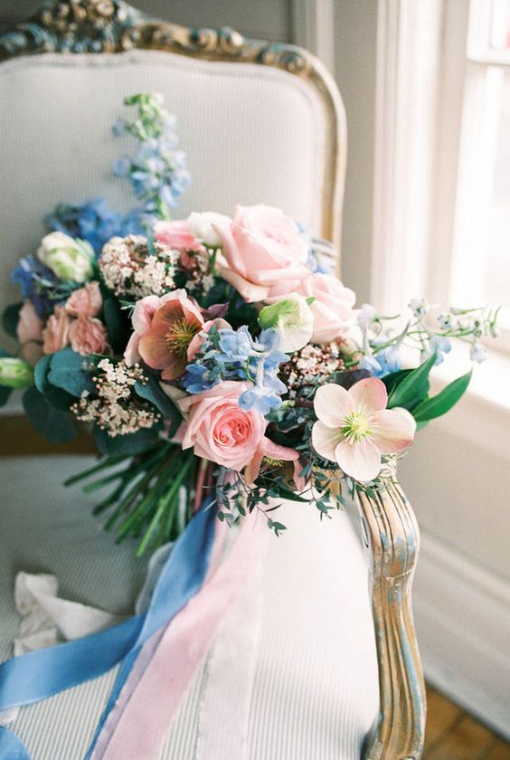 a lush pastel wedding bouquet in light blue and pink with matching ribbons hanging down