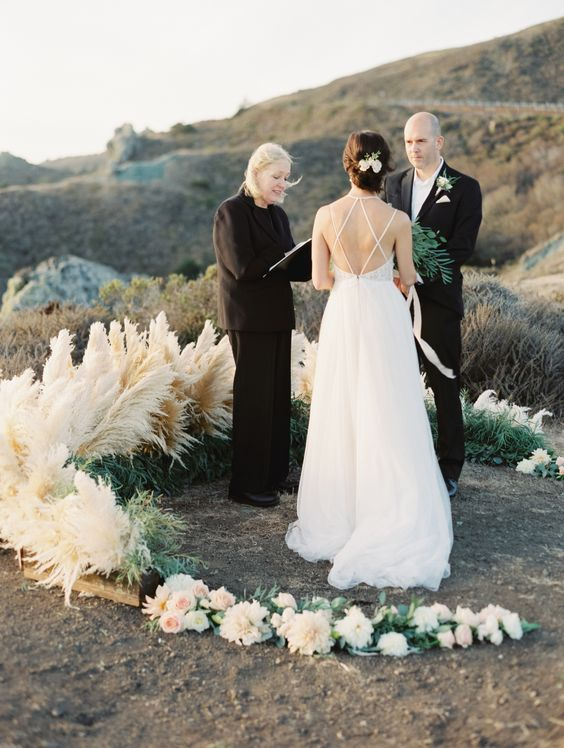 a lush semi circular wedding altar of blush and white blooms, usual and pampas grass