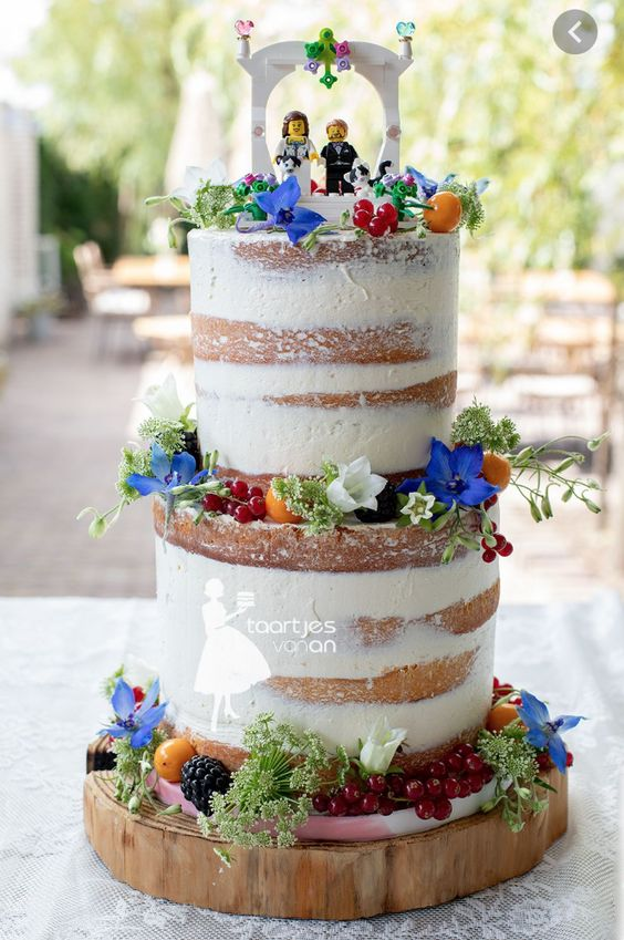a naked wedding cake with colorful and white blooms, berries and fruits and some Lego toppers