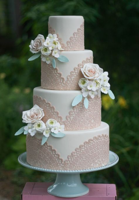 a neutral wedding cake with blush lace decor and sugar and fresh blooms for decor