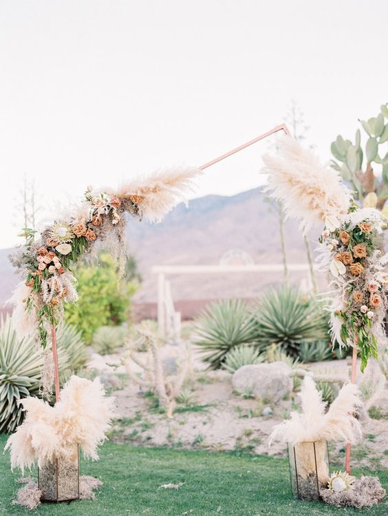 a non-traditional wedding arch of copper, with an irregular geometric shape and lush pastel blooms and foliage