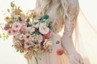 a pastel-colored wedding bouquet with red, blush, rust blooms and some greenery