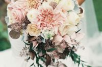 a pastel pink wedding bouquet with dahlias, roses and dark leaves to make a contrast
