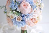 a pastel wedding bouquet in blush and pastel blue plus greenery and some neutral blooms