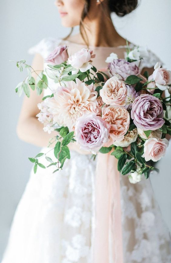a pastel wedding bouquet of peachy and lilac blooms plus greenery is a chic and tender idea for a soft look
