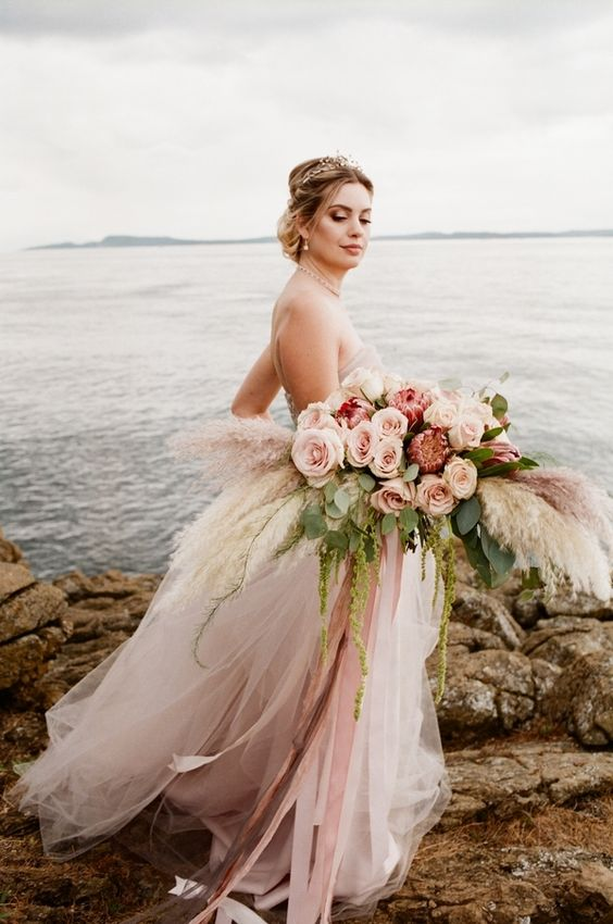 a pastel wedding bouquet with blush roses, pampas grass and king proteas will make a statement