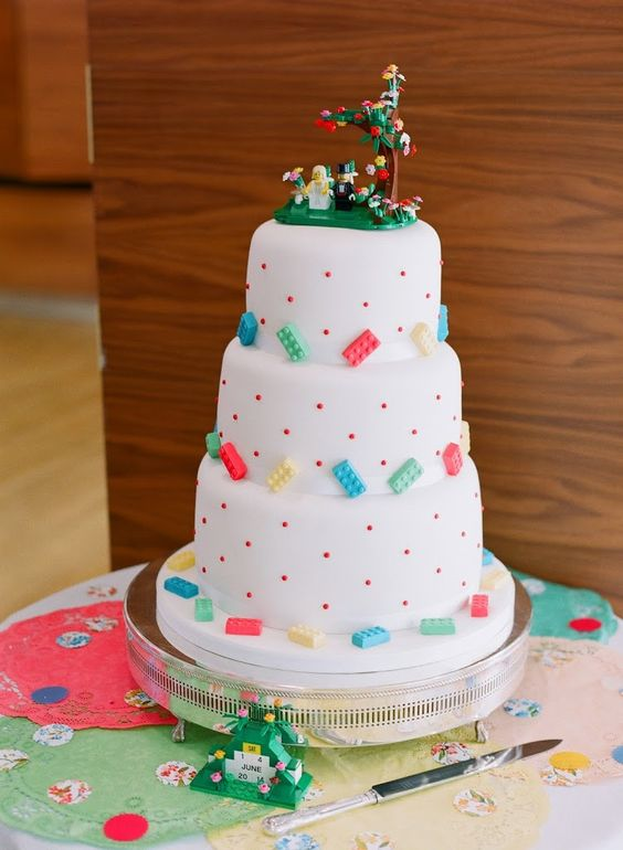 a playful wedding cake in white, with colorful Legos and creative cake toppers