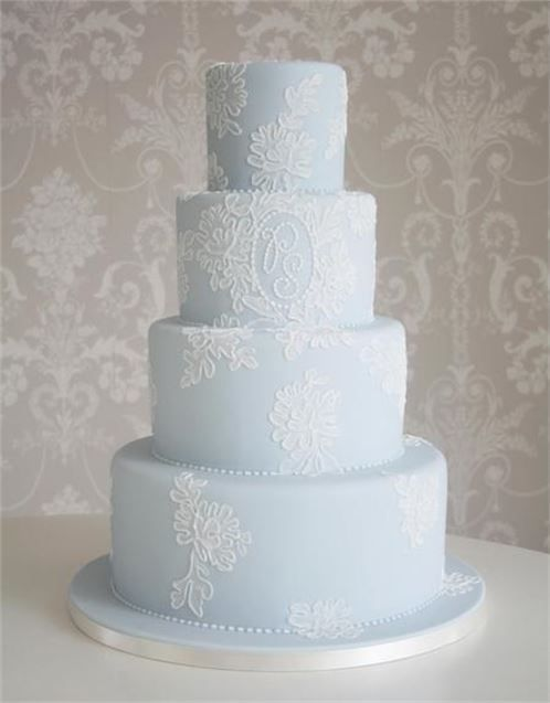a powder blue wedding cake with white lace and monograms is a pastel piece with a tender touch