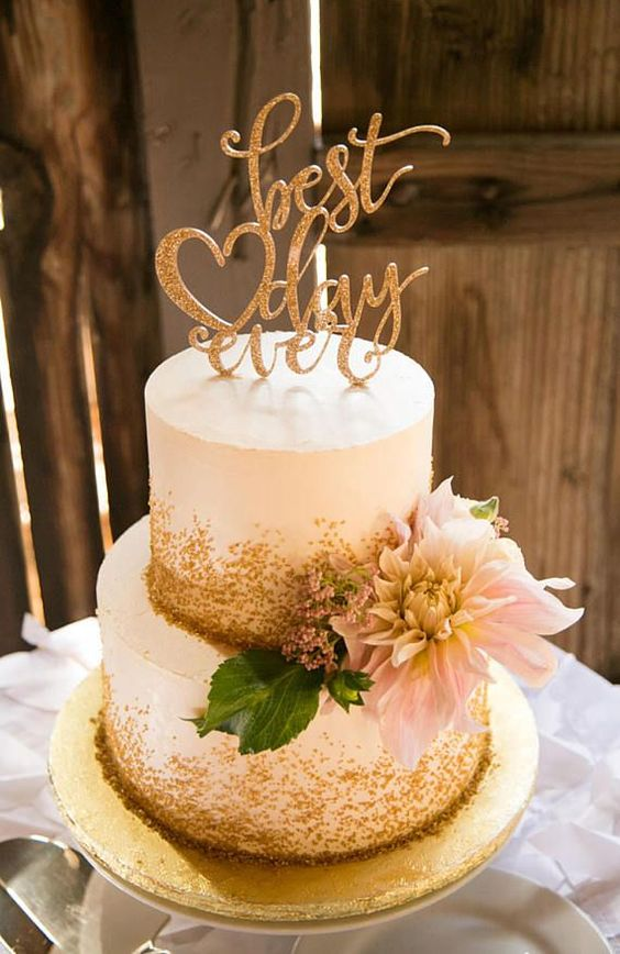 a pretty white and gold glitter wedding cake with greenery, berries and a pink dahlias, a gold glitter calligraphy cake topper
