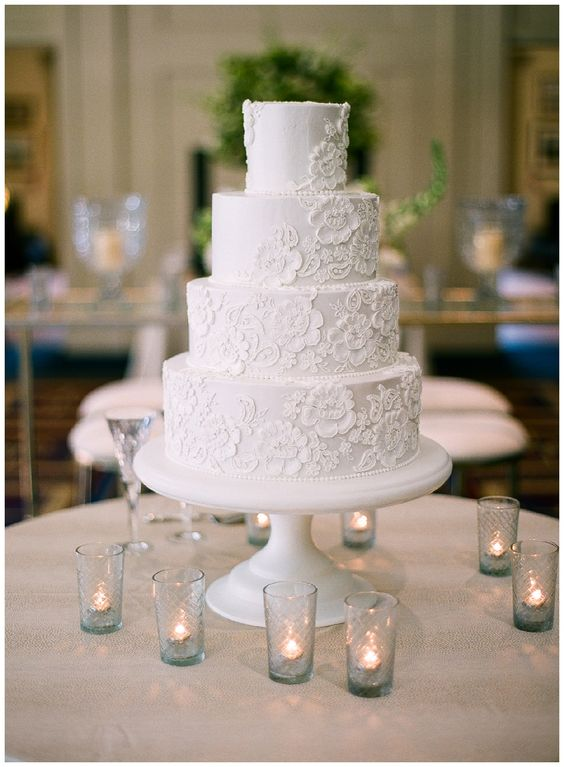 a purely white floral lace wedding cake accented with candles around is a sophisticated and elegant piece