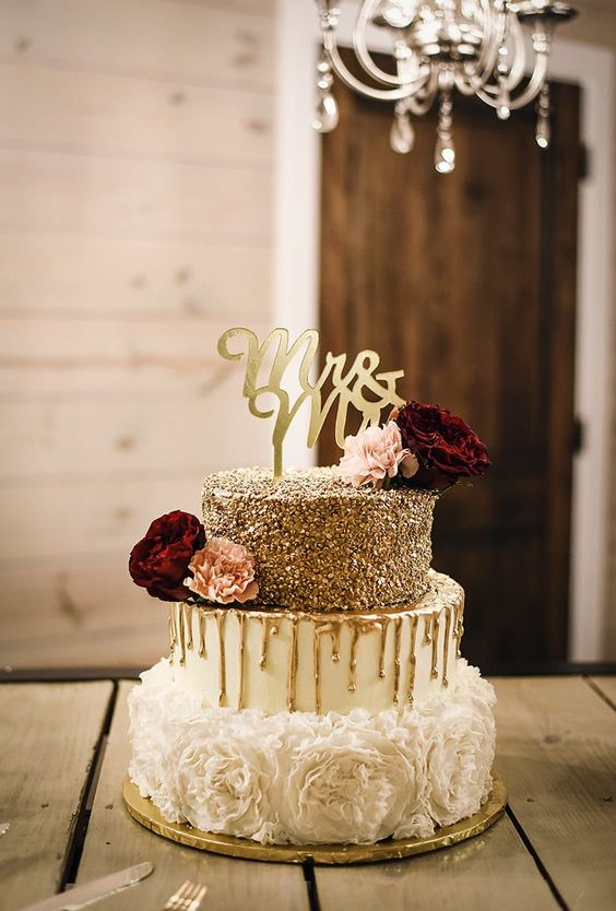 a refined and glam wedding cake with a gold glitter tier, a white one and a white flower one, with gold drip, burgundy and pink blooms and a calligraphy topper