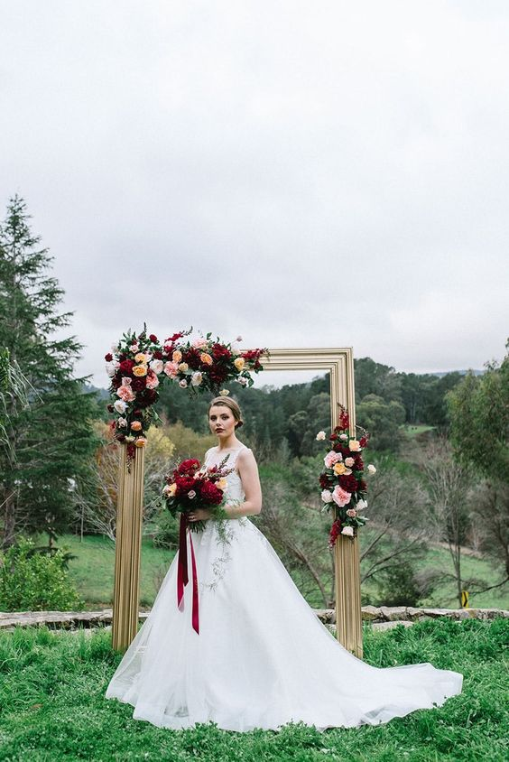 a refined wedding arch of a gold picture frame, bold burgundy, yellow and blush blooms and some foliage