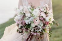 a romantic pastel wedding bouquet with white, blush and dusty pink blooms and long ribbons with a texture