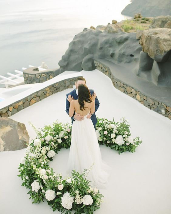 a romantic semi circular wedding altar of greenery and white blooms is a chic piece to tie the knot at