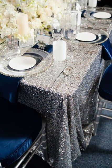 a silver glitter wedding tablecloth paired with navy anpkins, white blooms and candles and silver cutlery for a super glam and shiny tablescape