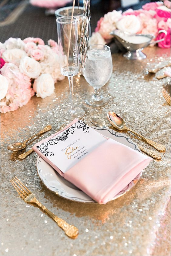 a silver tablecloth, pink napkins, a menu, blush and white blooms, gold cutlery and candles are lovely for a glam tablescape
