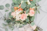 a simple wedding bouquet with blush and coral roses and eucalyptus with blush ribbons
