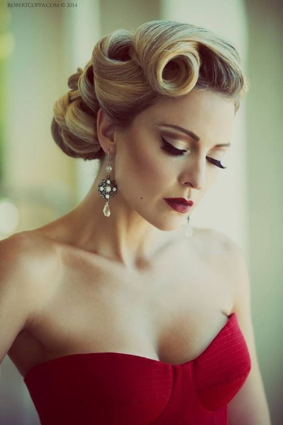 a statement vintage wedding hairstyle with curled sleek volumes on top is a jaw dropping option