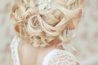 a stunning low wedding updo on long hair with a shiny rhinestone hairpiece and a slight volume on top