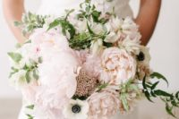 a sweet pastel wedding bouquet of blush and white blooms plus greenery and berries for a spring or summer bride
