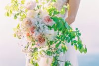 a textural and dimensional wedding bouquet with bold greenery and some blush peonies