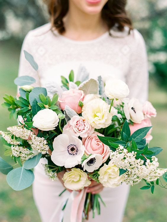 a textural wedding bouquet with pink and white roses, white anemones, greenery and some little blooms