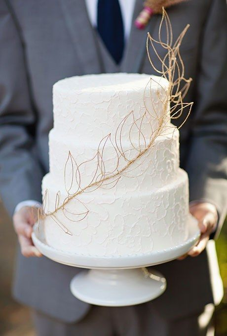a three tier white lace wedding cake with gold leaf detail is a simple and elegant option for your big day