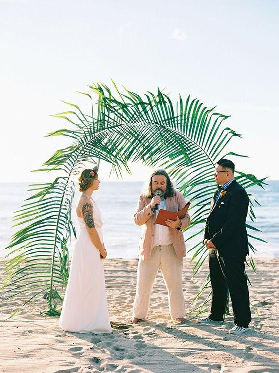 a tropical wedding arch of giant fronds is a cool idea for any kind of tropical or beach wedding