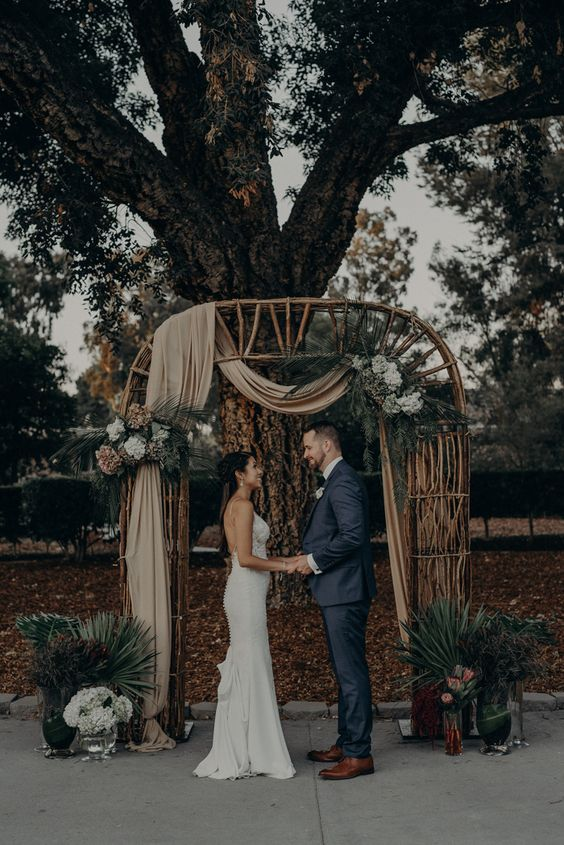 a unique boho wedding arch of rattan, with tan fabric, white and gold blooms, greenery and blooms in silver teaware