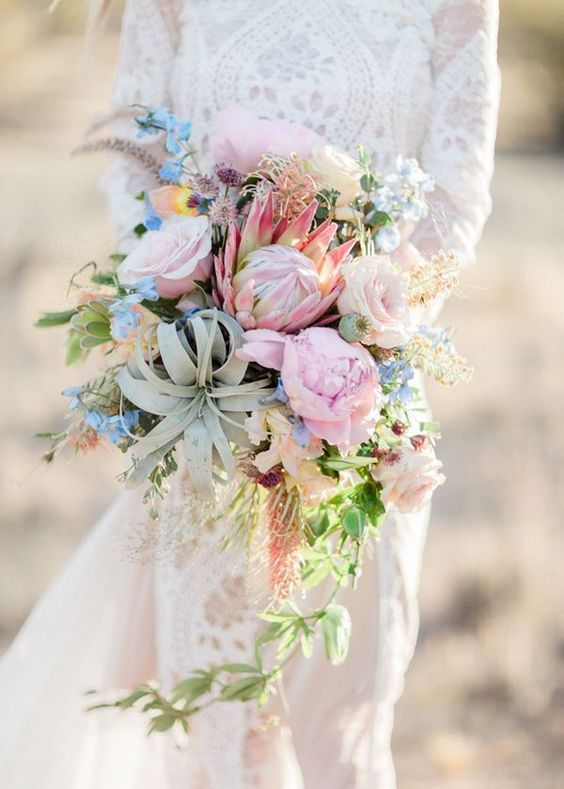 a unique cascading wedding bouquet in light pink and blue plus some neutrals, an air plant and much greenery